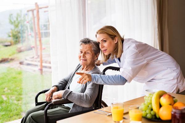 Pflegerin kümmert sich um Frau im Rollstuhl